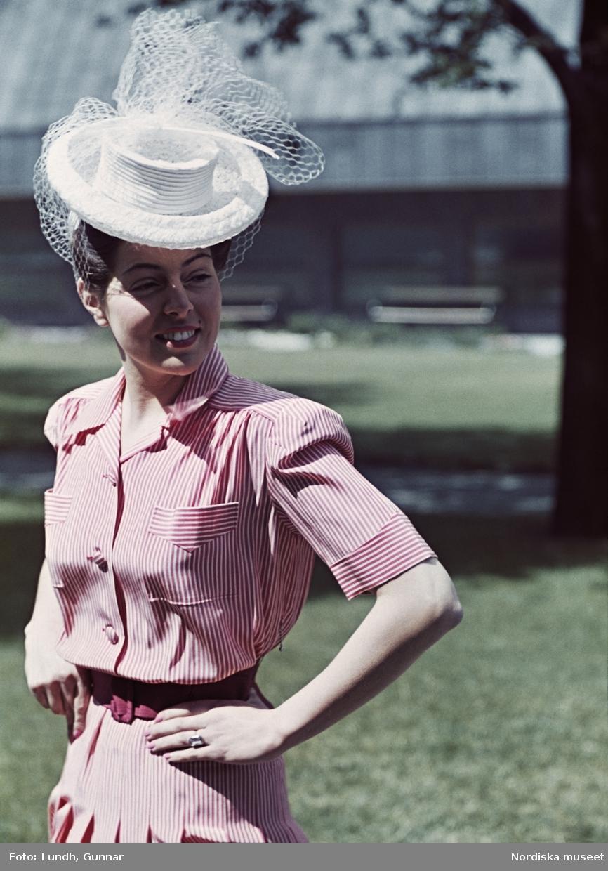 Kvinna i rödrandig klänning med skärp och vit hatt med flor.