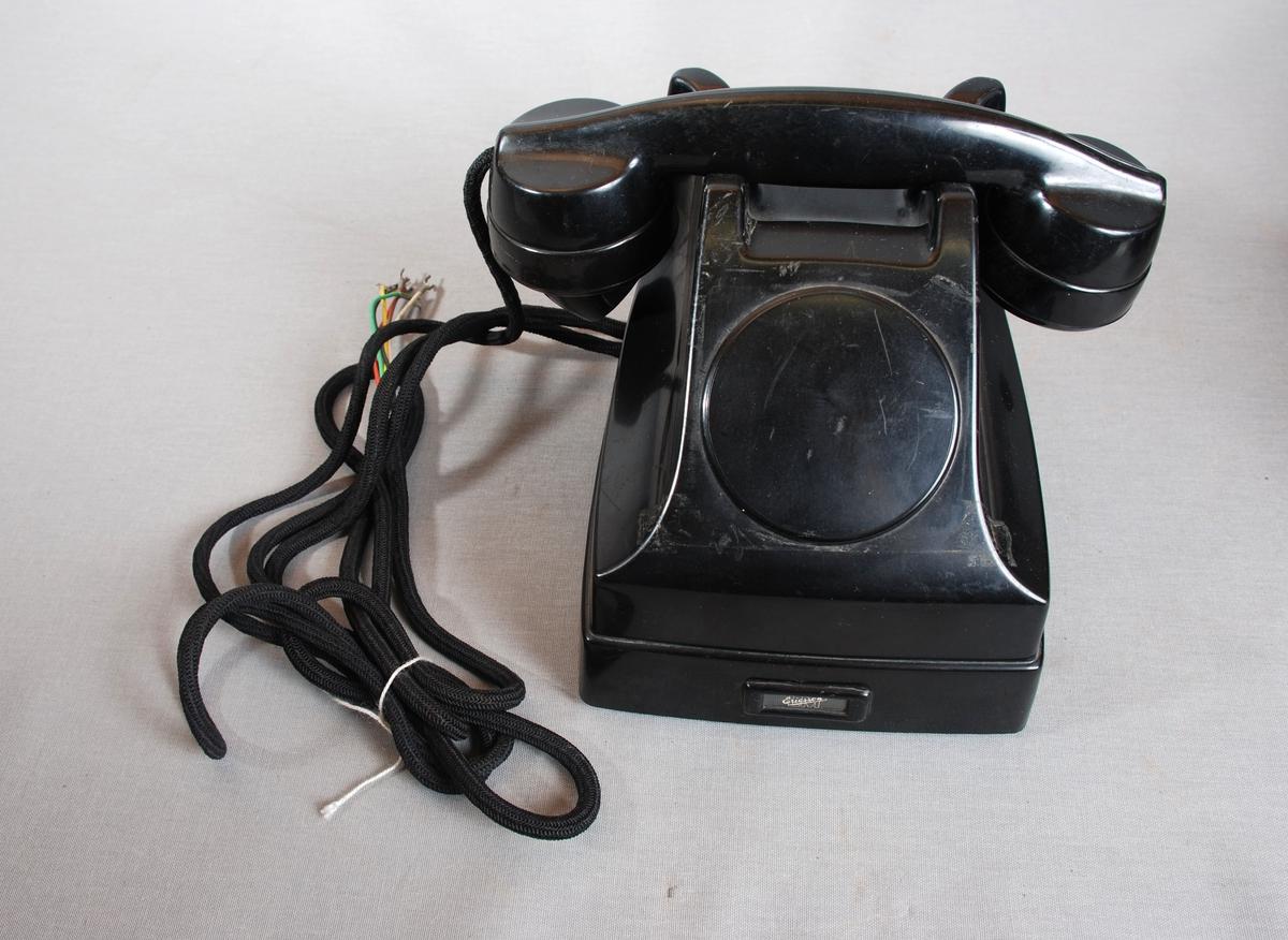 Telefonapparat med telefonrør på gaffel med kontakter/brytere. Ledning uten kontakt for veggfeste. Apparatet har firkantet grunnform, skrånendeoppover på fremsiden med plass for rund nummerskive. Denne plassen er dekket av en rund plate. Hull i siden for sveiv.