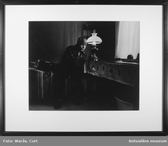 Ödemarksjul. Johan Lund, spelman på Kynnefjäll tänder sin fotogenlampa för julkväll i ödemarken. December 1973.