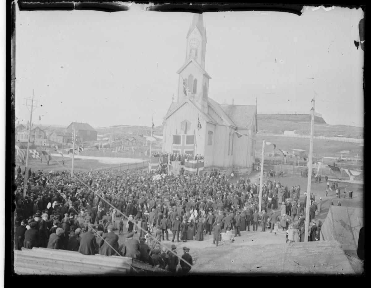 Dette kan være en 17.mai-feiring i Vardø en stor folkemengde samlet utenfor kirka. På kirketrappa er det laget talerstol og pyntet med flagg. Bak kirka ser vi deler av kirkegården og Klondyke. I forgrunnen ser vi remser med signalflagg hengt opp som utsmykning