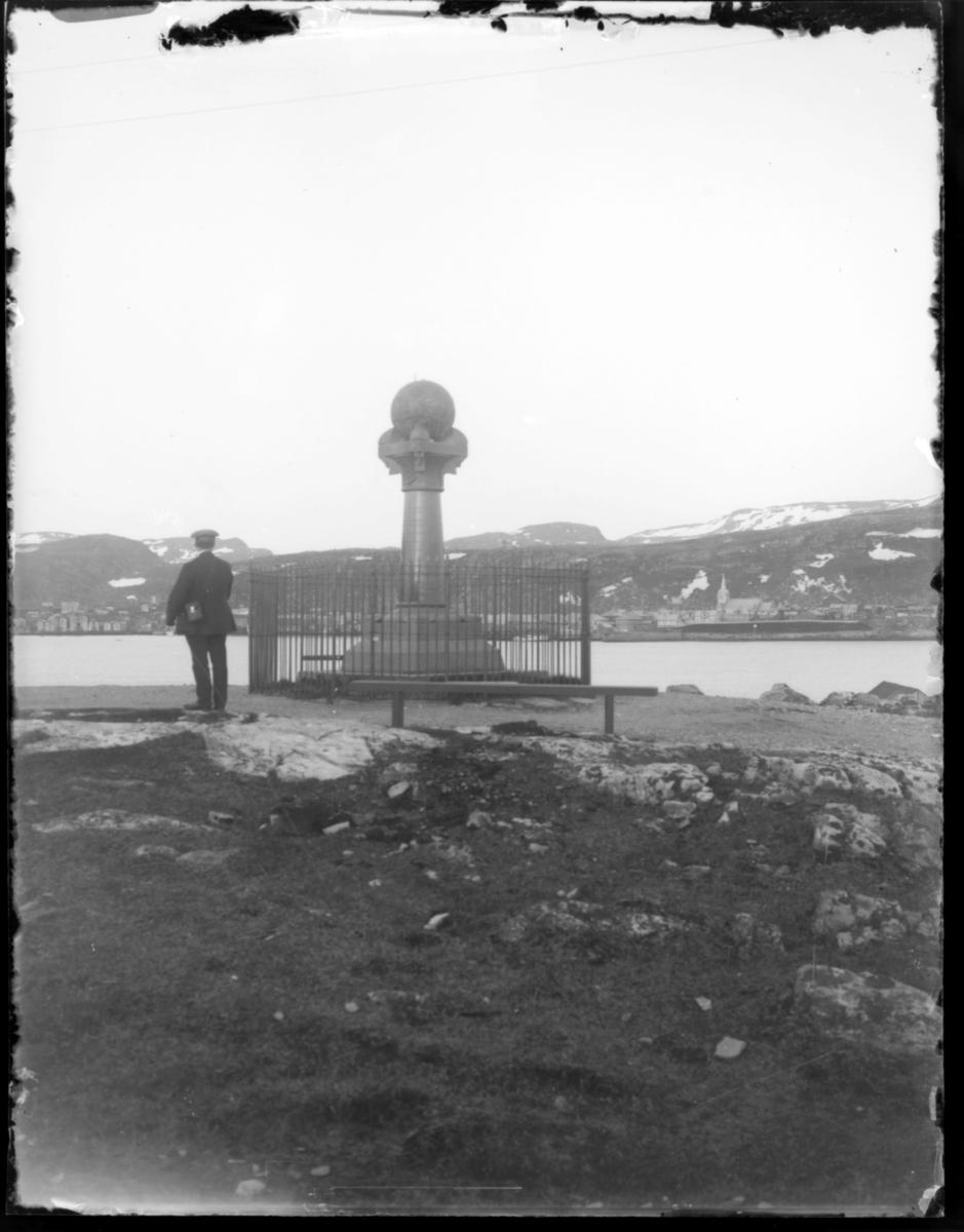 Meridianstøtten på Fuglenes i Hammerfest. En mann står med ryggen til kamera og ser mot sentrum av Hammerfest