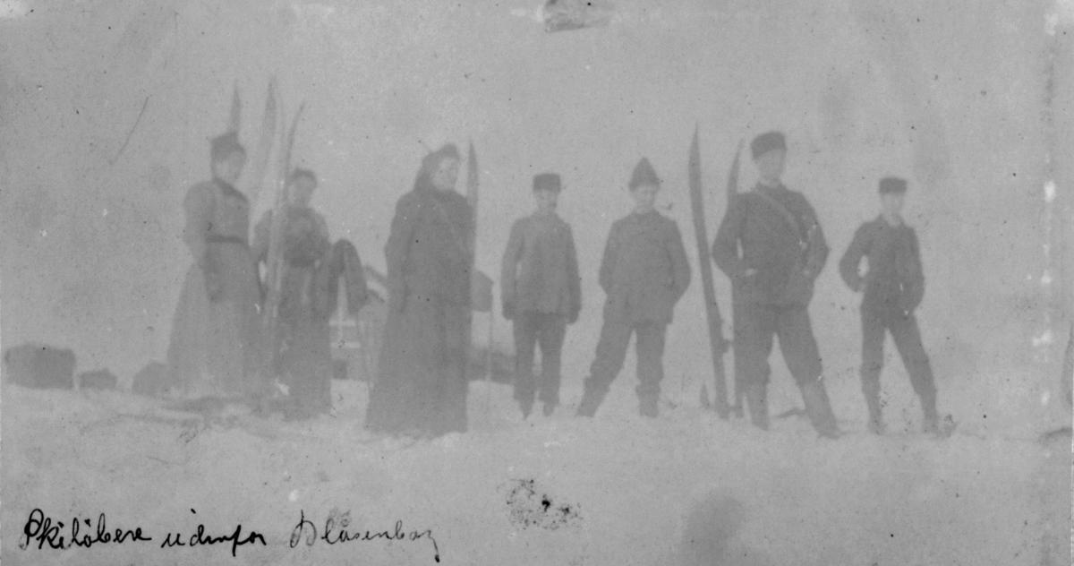 Skiløpere utenfor Blåsenberg. Fire menn og tre damer står i snøen. Damene har side kjoler. Ski står satt ned i snøen.