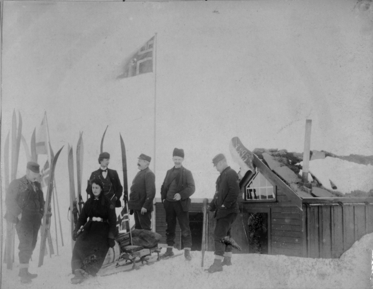 Menn og damer utenfor en hytte. En kjelke med en tønne, sekker og et flagg.. En dame sitter foran på kjelken. Det er ski stablet i snøen.