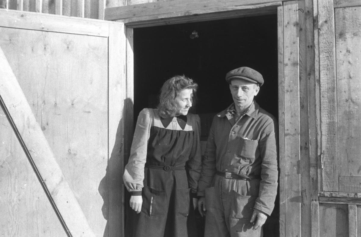 To personer i arbeidsklær står i en døråpning iført arbeidsklær. Sted og personer er ukjent.