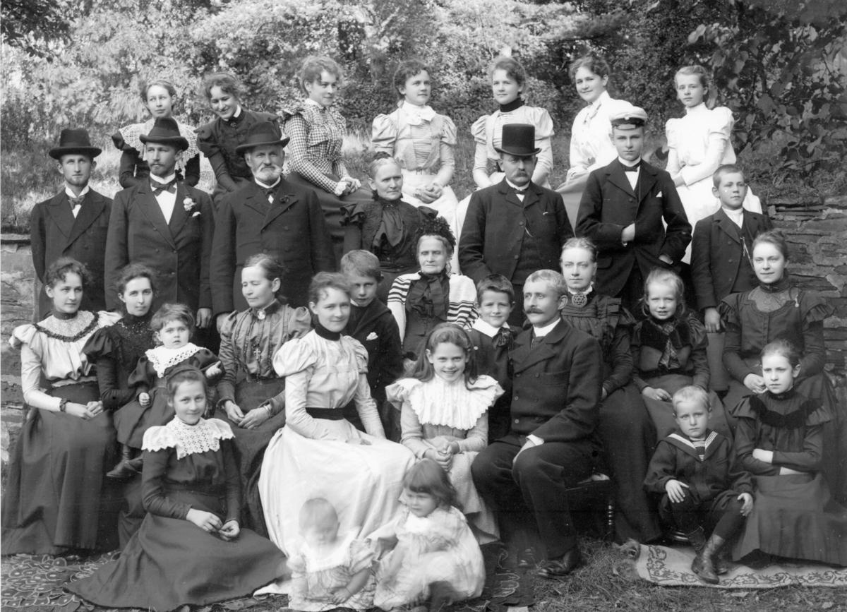 Fotoarkivet etter Gunnar Knudsen. Gruppebilde. Søsknene Jørgen Chr., Serine og Gunnar Knudsen med ektefeller og barn. I midten sitter søsknenes mor Gurine.
