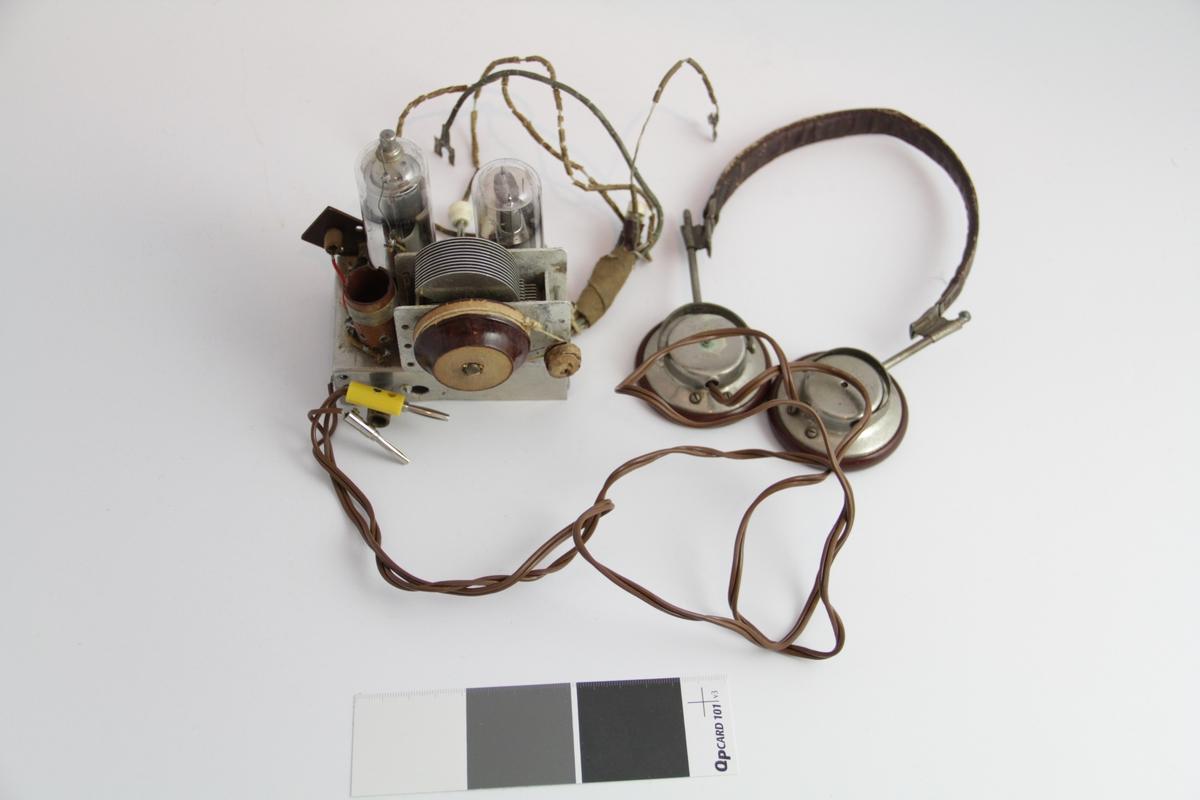 Form: Rektangulært chassi av aluminium påmontert synlig to radiorør,  spole, dreiekondensator som kan fininnstilles ved hjelp av en snor som går rundt en sylindrisk trekloss på dreiekondensatoren og en aksel laget av en spiker påsatt en rund treknott. Ledninger for tilkobling av batterier. Uttak for høretelefon og for antenne og jord. Skjult under chassi er det elektroniske komponenter som kondensatorer og motstander koblet til sokler for radiorør.
