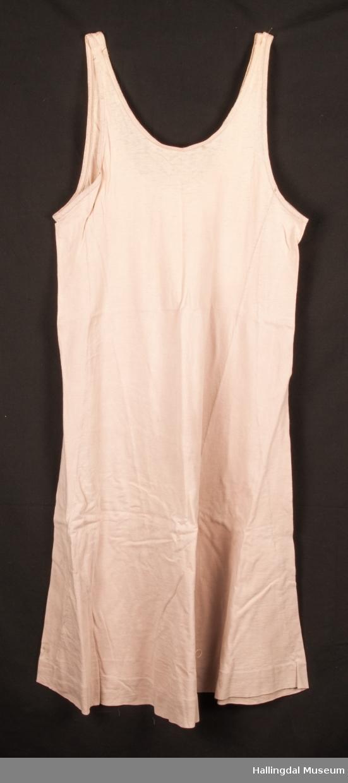 En ankelsid bomullskjole for dame. Eventuelt underkjole. Sydd av fire stoffbiter. Bred oppbrett nederst. Godt brukt - og både farge og søm er merket av slitasje. Vaskeseddelen er litt uleselig. Rift på side foran. Uformelig/ vridd.