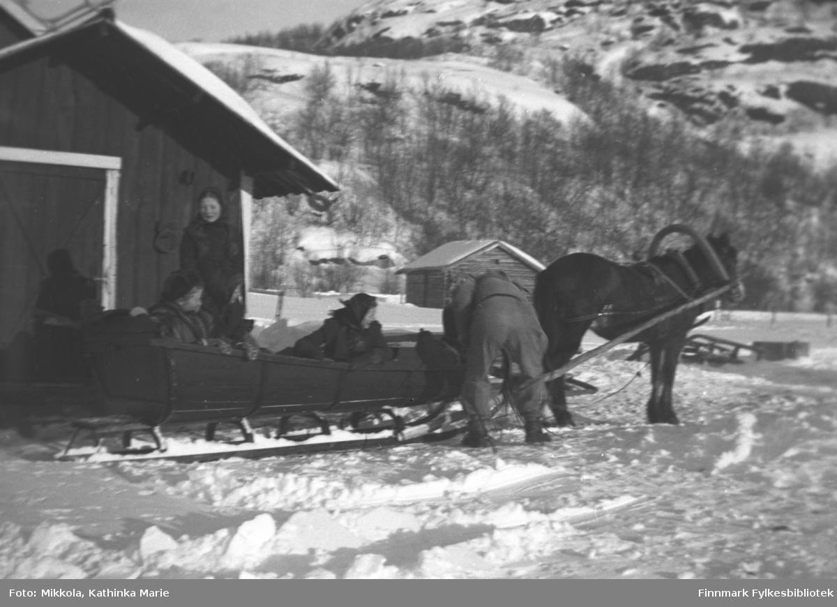 Borken med østfinsk bogtre står forspent stasriska. Kusken Andreas Mikkola med ryggen til kamera ordner med kjøretøyet. Bakerst i sleden sitter Synnøve, og foran Astrid Mikkola. Kari Mikkola står ved sleden. Bildet er tatt i mars 1934, ved samme anledning som 05007-052