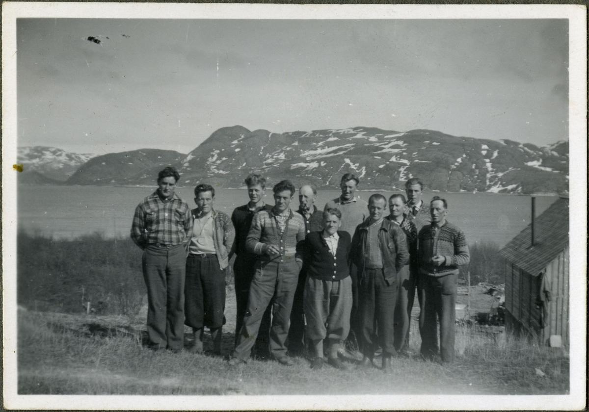 Ukjente menn poserer for et gruppebilde. De er trolig arbeidere på skiferbruddet i Friarfjord. Enkelte av mennene er kledd i strikkede jakker med mønster. Andre har på seg helt vandlige jakker. De er alle kledd i skjorter og bukser. I bakgrunnen kan man se havet og fjell. Enkelte av mennene holder på tobakkspiper. Helt til høyre kan man se et tre bygg med pipe. Det er blitt hengt opp klær på veggen.