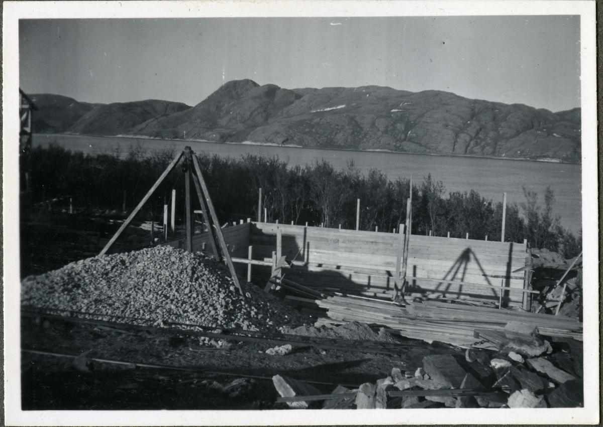 Konstruksjon av bygning på skiferbruddet i Friarfjord. Bygningen er trolig kantinen på skiferbruddet. På kantinens venstre side kan man se brakkene til arbeiderne. I området kan man se byggematerialet, og i bakgrunnen kan man se havet og fjell.