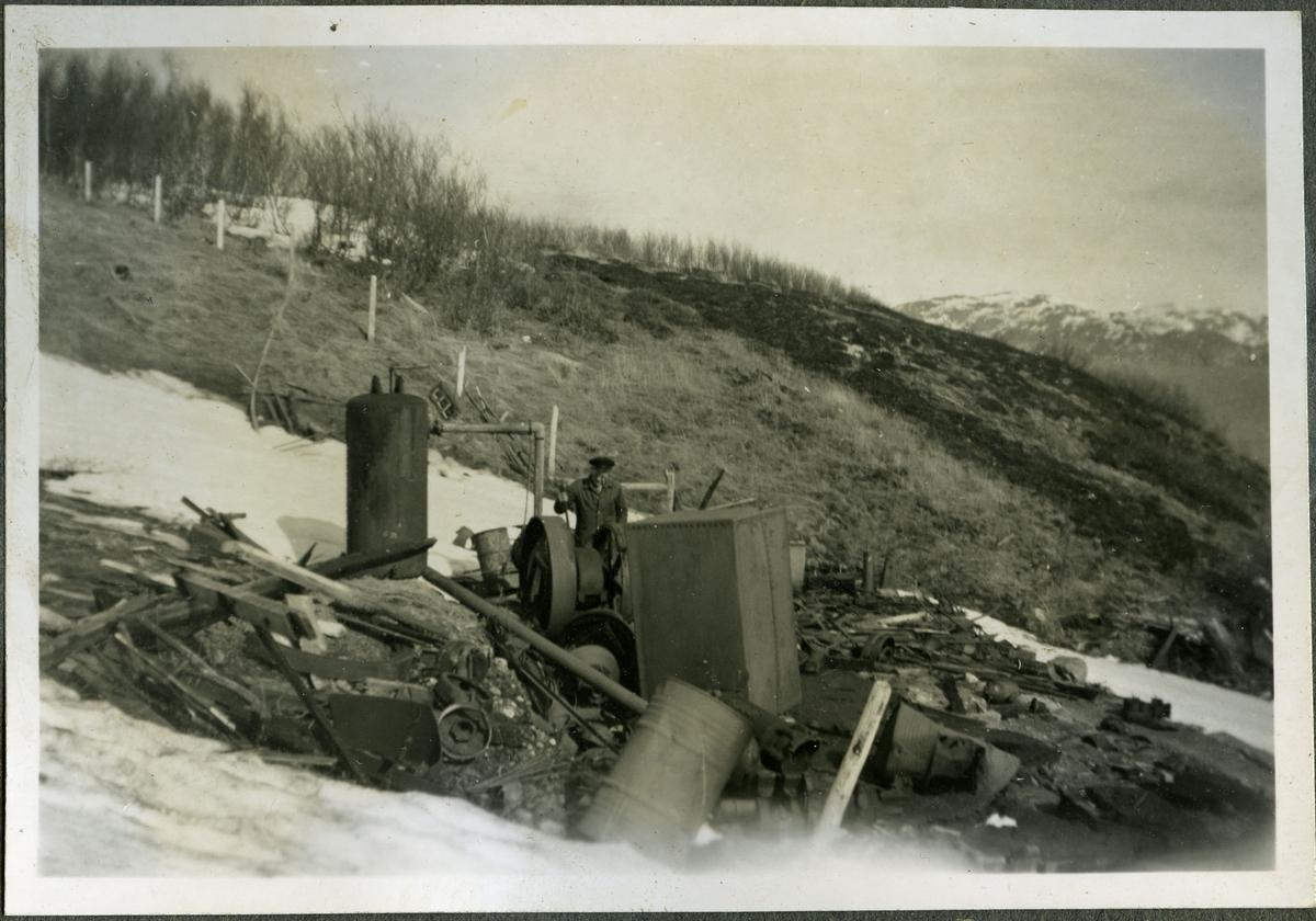 Fotografi av en metalltank og andre rester i fjæra på skiferbruddet i Friarfjord. Ved siden av tanken kan man se en mann som holder en stokk. I bakgrunnen kan man fjell og et gjerde.