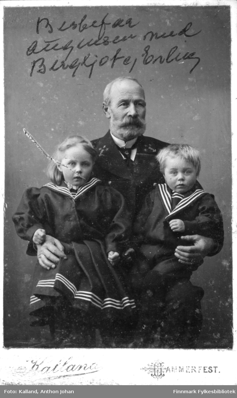 Portrett av en mann, Johan Theodor Augensen, som holder to små barn, Bergljot og Erling Buck, på hver sin arm. Han er iført en mørk dress med hvit skjorte og slips. Barna har mørke klær med lyse striper oppe og nede på draktene.