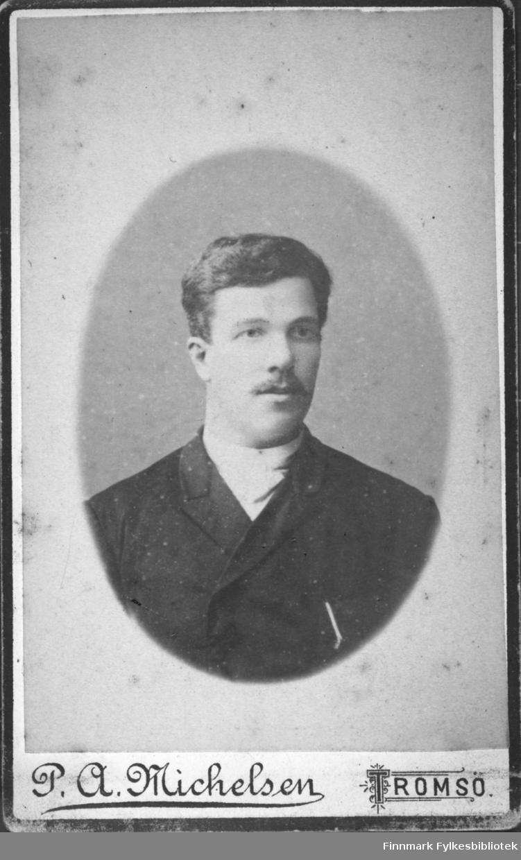 Portrett av en mann iført en mørk jakke. En lys genser eller tørkle ses rundt halsen hans.