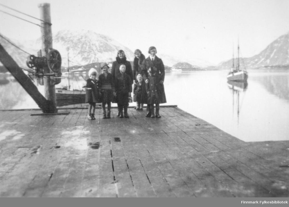 Tre voksne og fire barn på kaia i Bergsfjord. Damene har mørke kåper og barna har mørke klær og luer. Barnet til venstre har en hvit lue. Deler av en kran/vinsj til venstre på bildet. Bommen står på skrå ut fra festestokken. En wire går fra talja og ut og to går fra festestokken. En fiskeskøyte ligger fortøyd på den blikkstille havna rett bak folkene. En annen skøyte ligger fortøyd til høyre på bildet. Bak folkene ses en fjelltopp med litt snø på. En annen fjelltopp til høyre med noen snøflekker speiler seg i havflata.