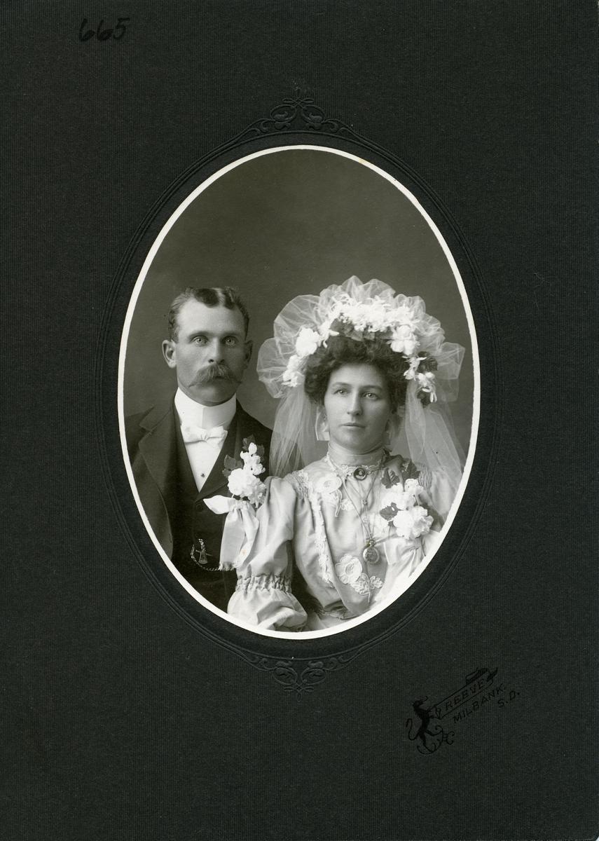 Bryllupsfotografi. Brudepar. Bruden har stor hodepynt med slør.