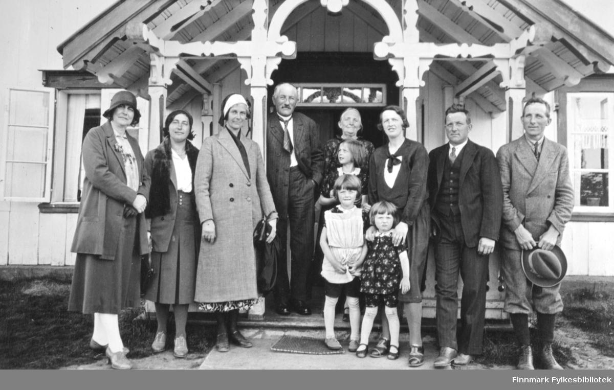 Åtte voksne og tre barn poserer foran en trapp/et vindfang. Alle har penklærne på seg. Mennen i dress, hvit skjort og slips. Han helt til høyre holder hatten i hendene. To av damene har mørke skjørt og kåpe. Hun til venstre har også hatt og hvite/lyse bukser. Trede dame fra venstre har mønstret skjørt, lang kåpe og tørkle på hodet. Barna har kjoler og strømpebukser og jenta i midten har i tillegg et forkle på seg. To todelte vinduer med sprosser på begge sider av vindfanget, et av dem står åpent. Stolpene til vindfanget har utskjæringer med en buegang i midten.