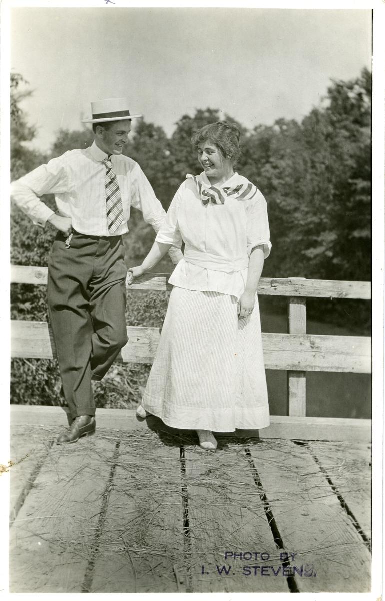 Mann og kvinne avbildet på ei trebru. Hun har langt hvitt skjørt og bluse. Han har mørtk buske, lys skjorte, slips og hatt