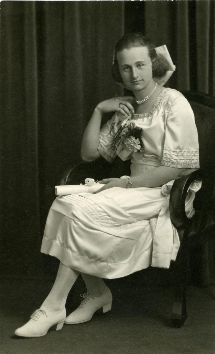 Kvinne sittende i stol. Ikledd hvit kjole og hun er pyntet. Mulig konfirmasjon?