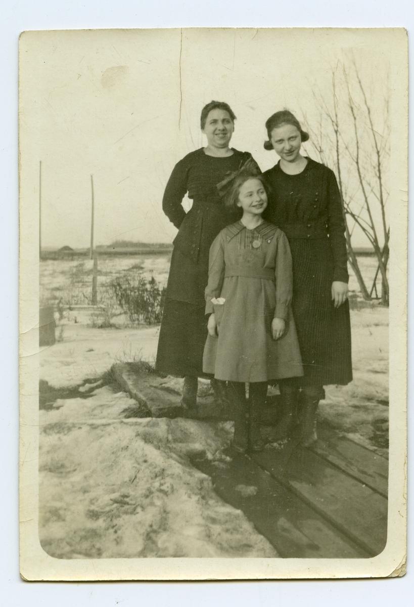 "Mor og to døtre fotografert ute. De står på noen sviller og det er snø rundt dem. Tekst bakpå bildet: ""Malla og hendes 2 jenter taget i 1917. Jentene er blevet så store og pene, men Malla er ikke stor af vækst"