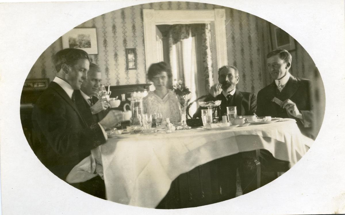 Postkort med motiv av en kvinne og fire menn sittende rundt et dekket bord. Hvit duk på bordet.