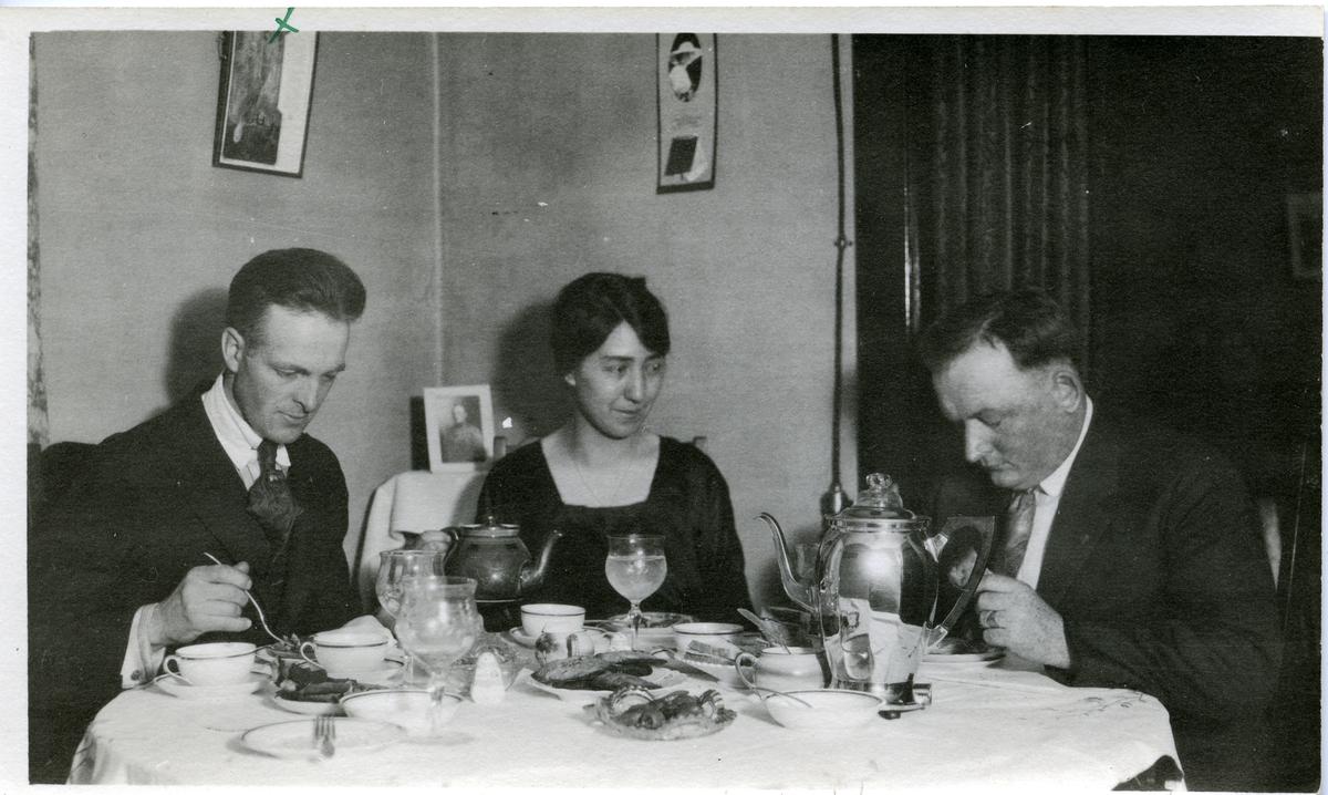 En kvinne og to menn sitter ved et pådekket spisebord. Kaffekopper, glass, kaker og kaffekanne på bodet.