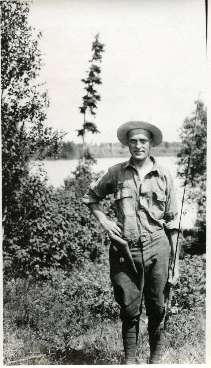 En mann som står foran et vann ikledd fiskeklær og fiskeutstyr