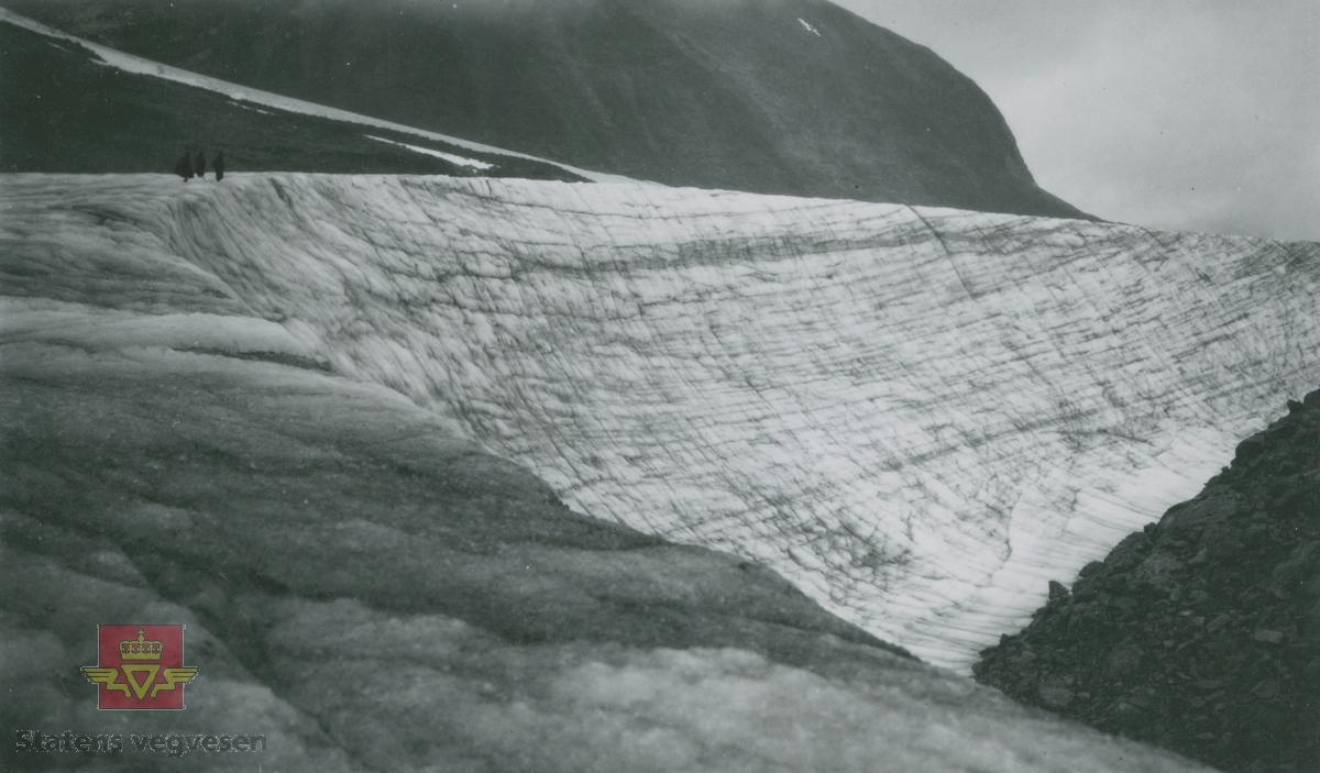 "Album fra 1929-1943. ""Ned for Tverrådalskirken mellom Nørstedalseter og Sota 1934."" Personer går ved isbreen."