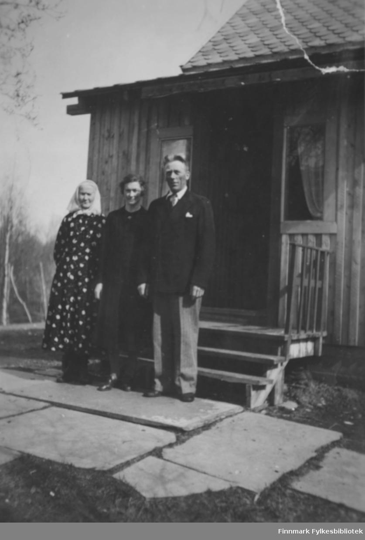 Utenfor huset på Gamnes. Nedenfor trappen på steinhellene står fra venstre: Karen Kristine Thomassen, kalt 'Moster', Karen Thomine Lovise Johansen f. Kristensen i mørk kjole, og hennes mann Andreas Julius Johansen. Han er kledt i en mørk dressjakke, hvit skjorte, og lyse bukser. De er foreldre til giver av bildene, Karen Kristine Jakobsen. 'Moster' som er kledt i en mønstrete kjole og et hvitt skaut, er Karen Thomine Lovises tante. Bildet er tatt av en tysk soldat som pleide å kjøpe melk av dem