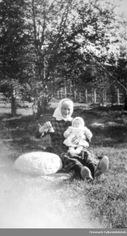 Karen Kristine Thomassen, kalt 'Moster' sitter på bakken foran trærne. På fanget holder hun giver av bildene, Karen Kristine Johansen g. Jakobsen. 'Moster' er tante til Karen Kristines mor. Bildet er tatt oppe på gården Fjellstad, øverst oppe i Tverrelvdalen. I bakgrunnen ses en del av et gjerde. 'Moster ' er kledt i en rutete kjole. På hodet har hun et hvitt skaut. I hånden holder hun en liten bjelle. Barnet er kledt i en hvit kjole og lue