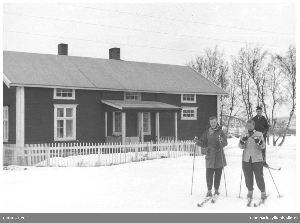 En gruppe folk poserer foran fjellstua i Polmak påsken 1957. De er muligens sykepleiere fra sykehuset i Vadsø. De har på seg luer, jakker, bukser og ski. I hendene holder de skistaver. Fjellstua er omringet av et gjerdet. På huset kan man se vinduer og skorstein. Bak huset kan man se trær og bakken er dekket til med snø.