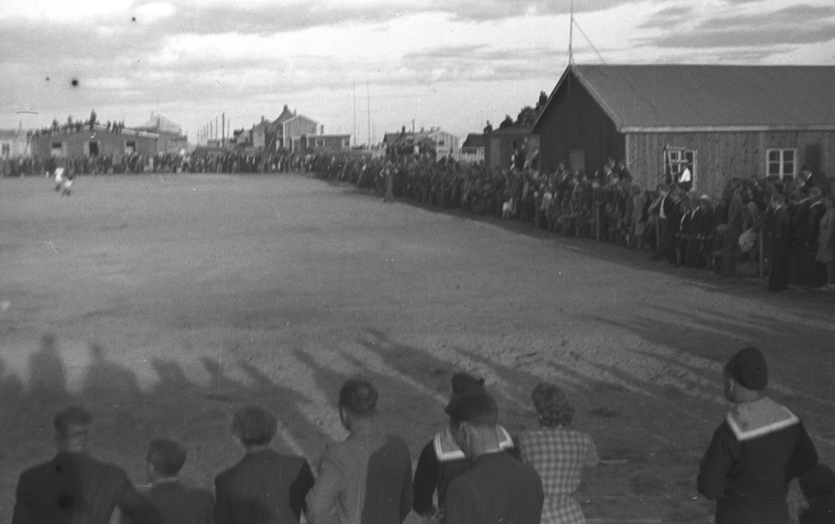 Fotballkamp på Indreby-banen i Vadsø. Lag, spillere og tilskuere er ukjent. Brakker og boliger står nesten inntil banen og tilskuerne står tett i tett langs banen.