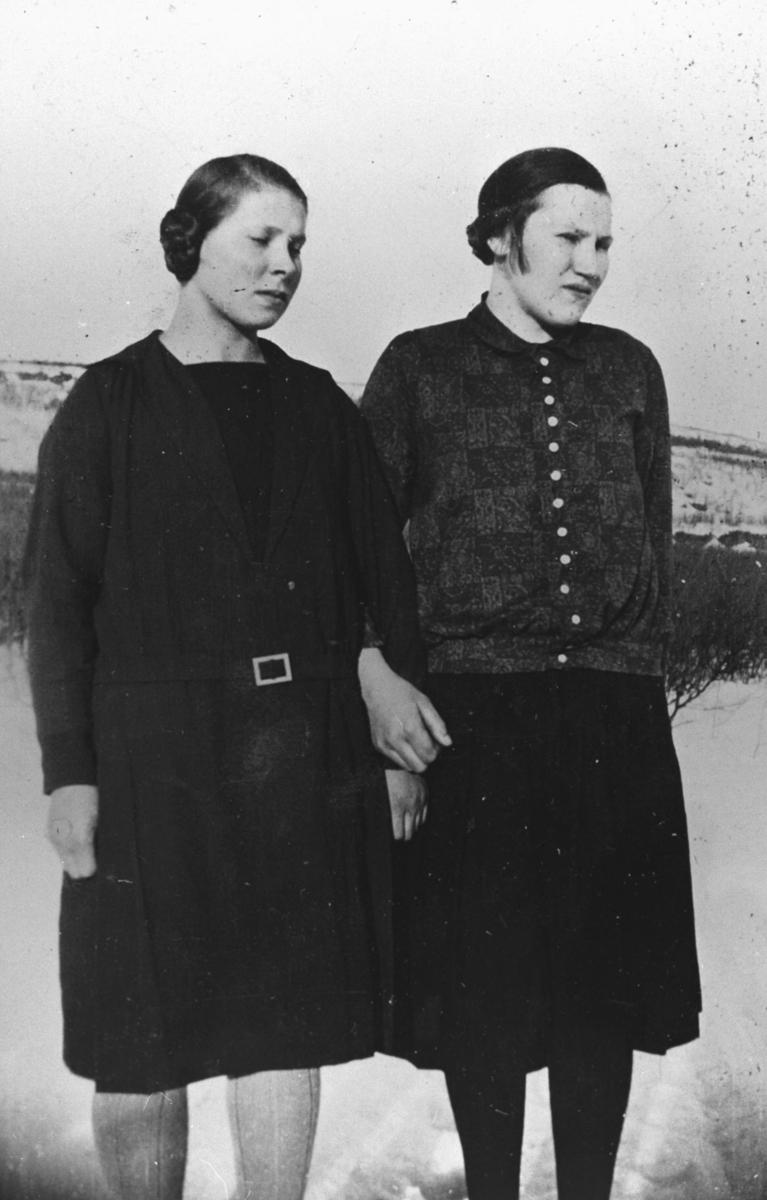 To unge kvinner, (fra venstre) Elna Mietinen (f.Malmstrøm) og Emma Aleksandersen, fotografert ute på en solig vårdag. Dem holder varandre på handen, Elna lukker igjen øynene sine for det skarpe lyset. det er ennå snø på marken. Bildet er tatt fra nært avstand slik at