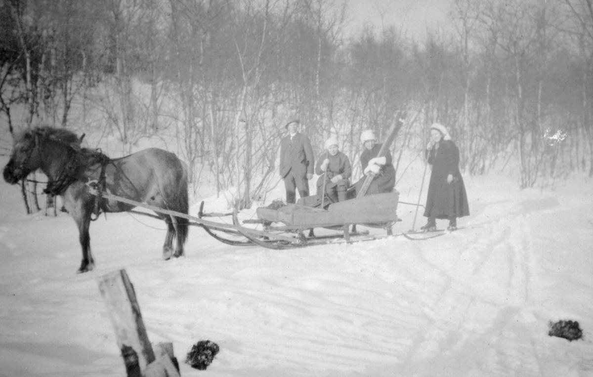 Hest og slede med mennesker. På tur fra Jarfjord til Knes. Flere kvinner og menn er kledd i vinterklær. En kvinne som sitter i sleden holder på et par ski, og kvinnen t.h for henne står på ski.