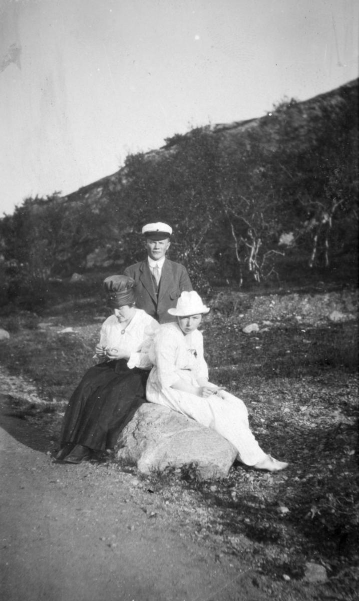 """""""Fra Soldatbukten. Knes."""" To kvinner sitter på en stein ved siden av en grusvei. De er kledd i kjoler. En ung mann står bak dem, og har en hvit hatt på hodet. I bakgrunnen kan man se skog."""