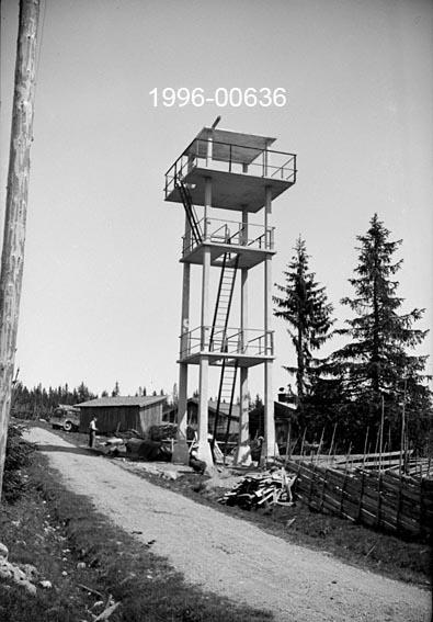 """Brannvaktstasjonen på Savalsætra i Løten.  Anlegget ligger ved en sætervang i en sørvendt del av allmenningen, cirka 11 kilometer fra Løten jernbanestasjon og om lag 530 meter over havet.  Tårnet gav fint overblikk over den søndre delen av Løiten Almenning og tilstøtende områder i Elverum og Våler kommuner.    Anlegget er utført i armert betong og i funkisperiodens formspråk.  Tårnet er cirka tolv meter høyt.  Det har et kvadratisk grunnplan og består av fire loddrette bein med støpte dekker i tre plan, samt et flatt tak.  Adkomsten fra bakken skjer via stålstiger som er ført gjennom rektangulære åpninger i de tre nederste dekkene.  Det øverste planet er noe utkraget i forhold til den nedre delen av tårnet.  Samtlige plan har kantrekkverk av stål.   Fotografiet er tatt fra en veg som skrår inn i bildeflata fra det nedre høyre hjørnet.  Langs vegen går en skigard.  I bakgrunnen skimtes et par graner og et sæterhus.   Brannvakttårnet på Savalsætra ble reist i 1935-36 i samarbeid med forsikringsselskapet """"Skogbrand"""" som hovedsponsor.  Entreprenør var selskapet A/S Betongmast, men hytta oppe i tårnet ble reist av Karl Galaas (1882-1962) fra Rakkestad i Østfold.  Plasserringa ble bestemt i samråd med allmenningsbestyrer Karsten Haugen (1879-1957) i Løten etter at Østoplandenes almenningers fellesforening hadde hatt befaring på ulike høydedrag i området sommeren 1935.  Organisasjonen omfattet allmenninger for bygdene Stange, Romedal, Løten, Vang, Furnes, Veldre, Nes, Ringsaker, Brøttum i Hedmark, samt Eidsvoll i Akershus, og i tillegg den såkalte Ekeberg-allmenningen i Romedal og Pihlske sameie i Ringsaker.  Det ble oppgitt at disse enhetene til sammen forvaltet 970 491 dekar med skog, hvorav 566 098 dekar ble vurdert som produktive arealer.  Allmenningene hadde allerede brannvaktstasjoner på Natrudstilen i Ringsaker, på Brumundkampen i Vang og på Knukberget i Stange.  Som supplement ønsket de en østligere stasjon, som også kunne stå i forbindelse med statsjonene på Flots"""
