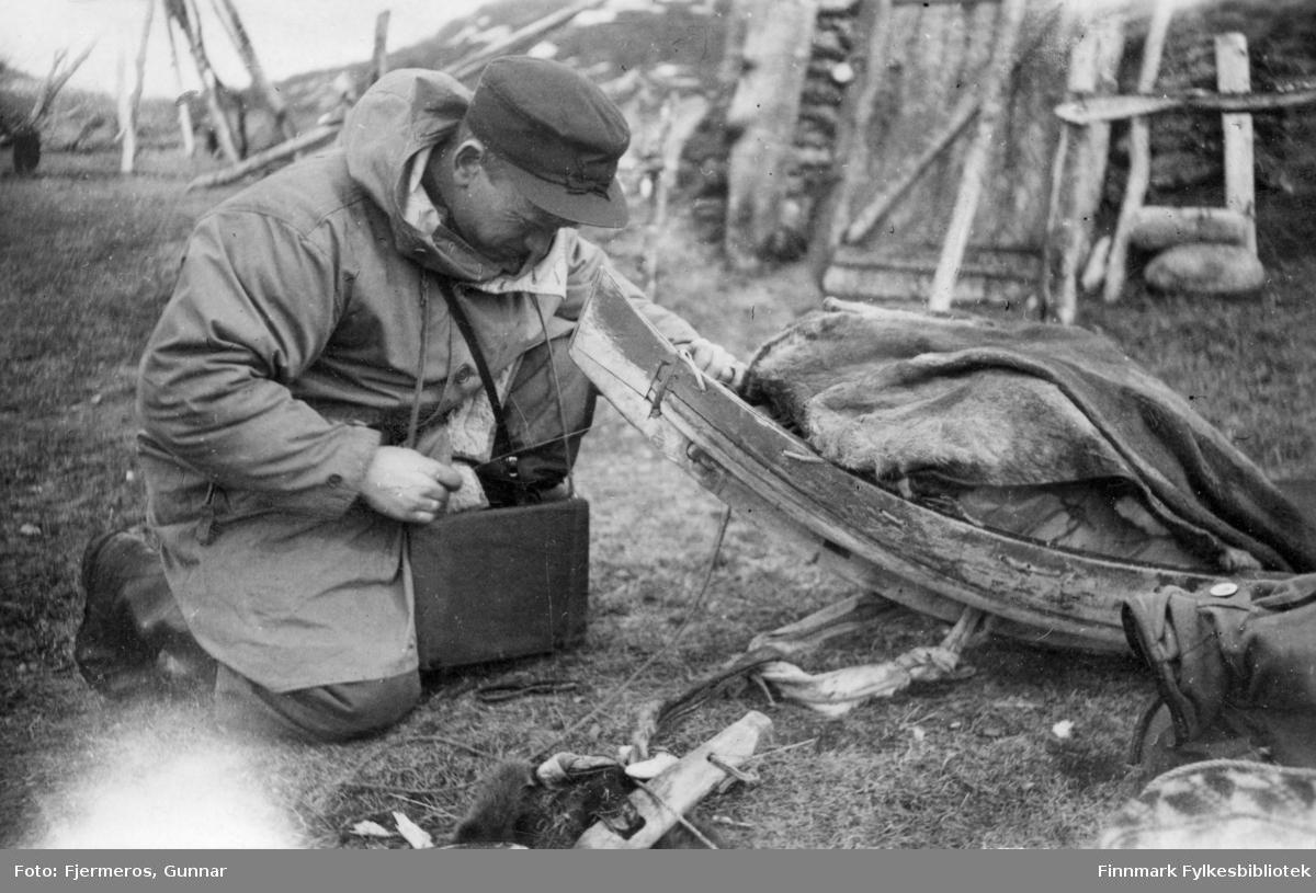 En mann sitter ved siden av en reinslede ved Levajok fjellstue en vårdag i 1948.