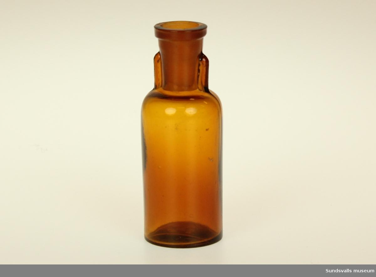 Brun glasflaska med avsmalnande hals och gjutna skänklar. I botten finns en i glaset gjuten triangel med siffran 20.