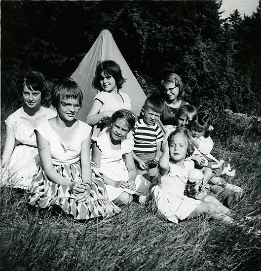 7/7 1959, mitt födelsedagskalas. Gäster vid mitt oranga partytält: Karin Molin, Britta Molin, båda Enköping, somrar i Smögen-Gravarne; Elisabeth Madgård; Inger Wetterlund; Martin Hansson f. 1953 Uddevalla (järnhandeln), sommar- granne; Ann Madgård; Misse Stoltz Norrköping, sommarhus med Hanson, f. 1948, lekte med Inger; Ulrika Hansson, yngre syster till Martin, med vackert kopparrött långt hår. Veronika med docka Kerstin i reskläder.