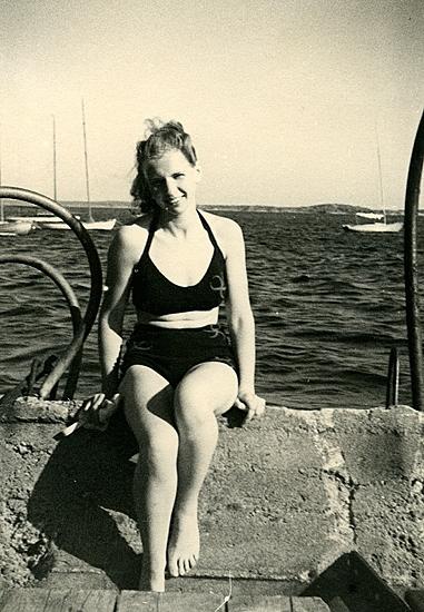 Sommaren 1940? Birgit i soldräkt. Vid cementklacken som inte längre är badplats, nu båtupplägg. Havsten i bakgrunden. Fotograf någon beundrare ? På väg till Ösö med båten ?.