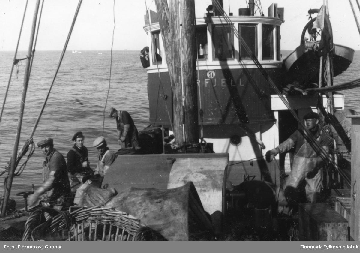 """Flere menn på dekket og i rorhuset på båten """"Varfjell"""" som er ute for å  fiske/fange Håkjerring. Mennene og stedet båten ligger er ukjent, men bildet er tatt sommeren 1948."""