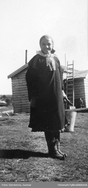 En samekone, Maja Biti, står foran et lite hus. Stedet er ukjent.