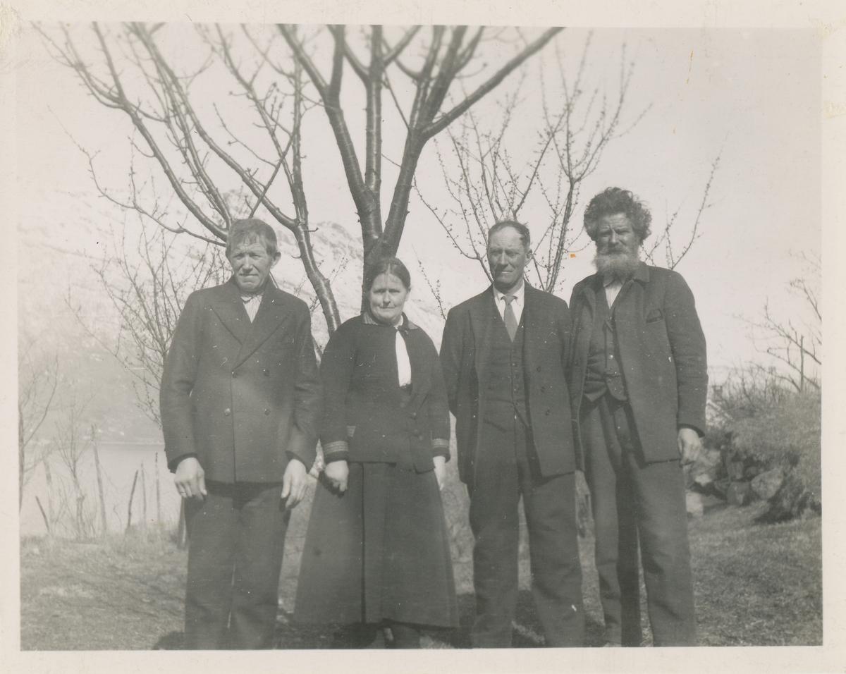 Tre menn og ei kvinne i finere klær poserer for et gruppebilde ute foran et tre.
