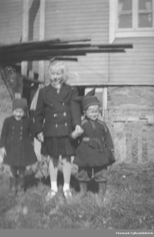 Tre barn poserer for fotografen en sommerdag. Barna og stedet er ukjent.
