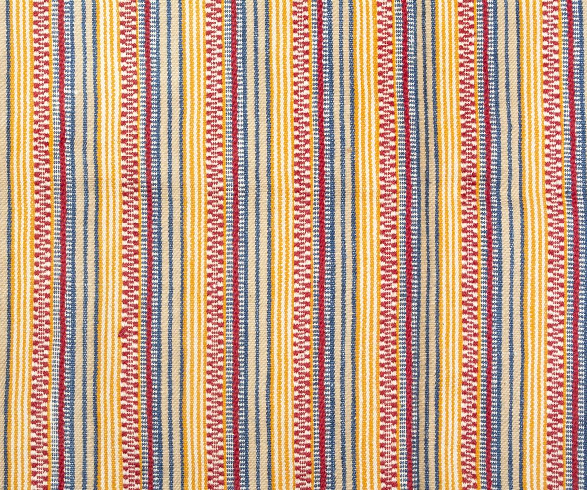 Långrandigt bomullsförkläde i gult, vitt, mellanblått, beige,rött och svart, i upprepade grupperade ränder. Upptill rynkat mot en linning av maskinvävt tyg, 4 mm smal fåll längs sidorna, 7 mm fåll nertill. Långsidorna har avslutats med vitt inslag till fållen. Vid linningen är handvävda knytband i blått, gult, rött, rosa och vitt, fastsydda. Banden avslutas med rak fåll.