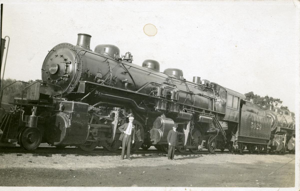 Bildet viser to personer foran et lokomotiv. Dette er et postkort.