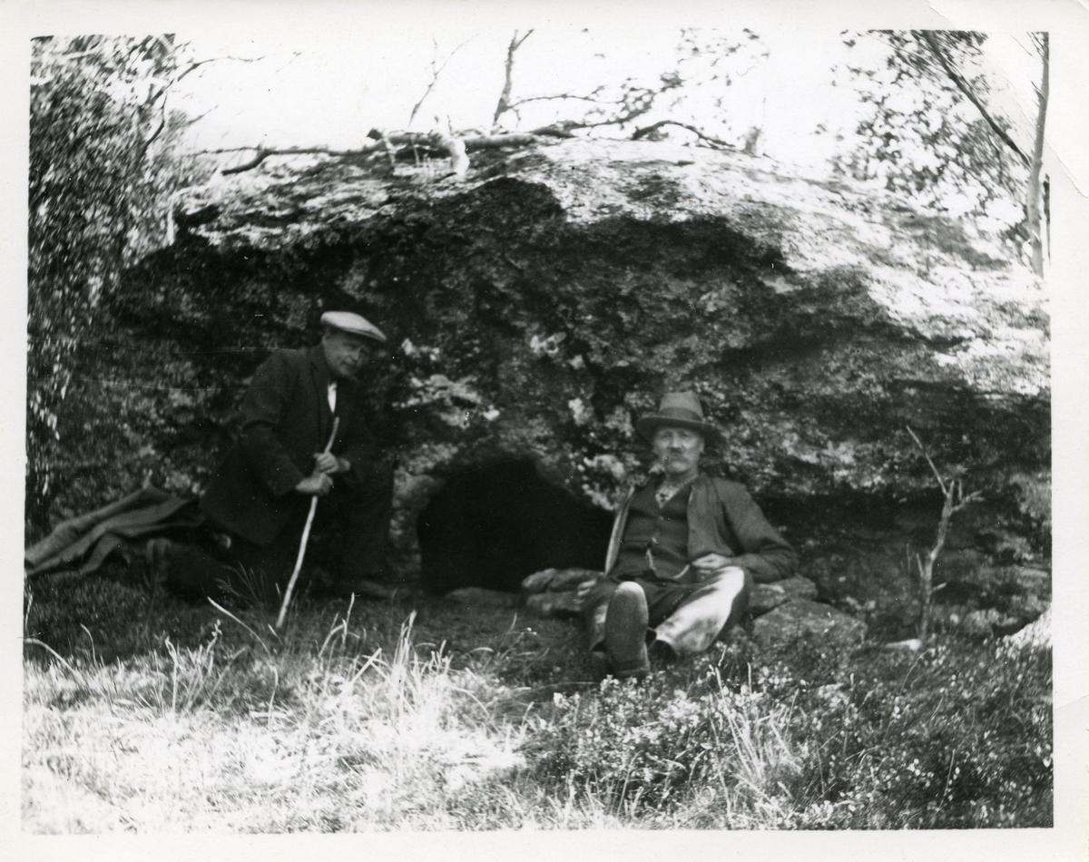 "To menn sitter under en stein. Steinen er sannsynligvis ""Verssteinen"" i Vang kommune."