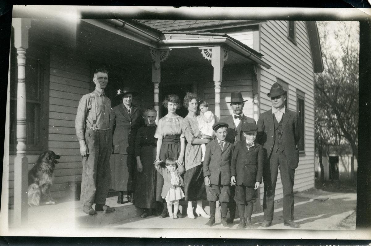 Portrett av en gruppe mennesker. Bildet viser tre menn og fire kvinner. I tillegg er det fire barn og en hund. To av mennene er iført dress og hatt mens den ene mannen trolig er iført hverdagsklær. Kvinnene er iført kjole. Barna er også iført penklærne.