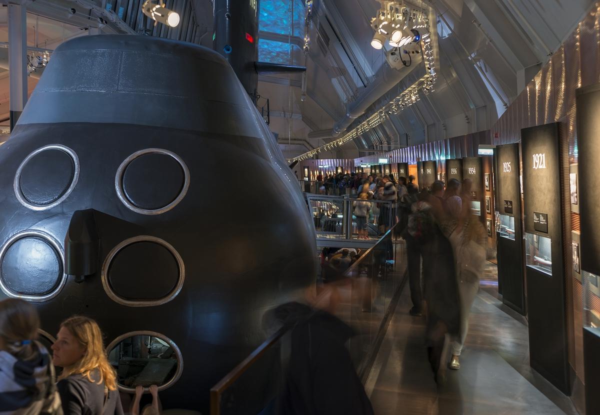 Marinmuseums ubåtshall med ubåten NEPTUN. Många människor på besök och som väntar på att få gå in i ubåten.