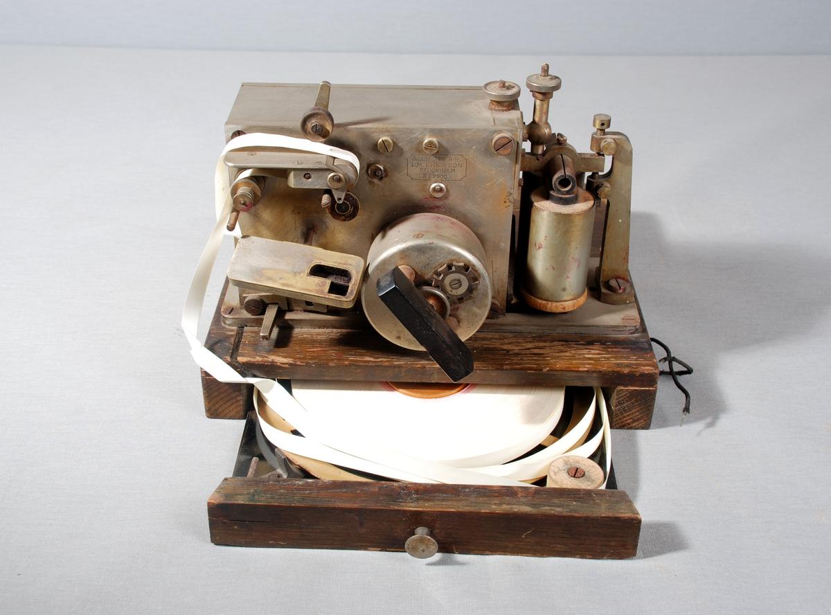 Maskin for mottak av signal fra offentlig (eller privat) brannmelder. Den registrerte nummer på brannmelder med streker på papirstrimmel plassert i egen skuff på undersiden av apparetet. a)er en trekasse påmontert metallmaskin, hendel i bakelitt. Et rundt glassvindu på grunnplaten viser papirstrimmel.  b) Treskuffefront med metallhåndtak, rundt messinghjul med papirstrimmel rull festet på
