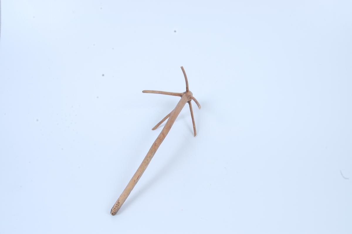 Form: trepinne/skaft, i ene enden er det en krans av fem pinner som går skrått ut fra skaftet